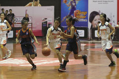 Basketball game between high school. Women's basketball player in action during a league match between middle school students in Solo, Central Java, Indonesia Stock Photography