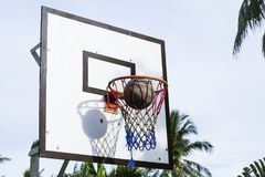 Basketball game outdoor equipment contrast photo. Accurate ball throw in basket. Stock Photos