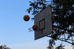 Two basketball balls being thrown into the basket at the same time. Basketball game on a sunny day on the street. Two balls are thrown at the same time in the royalty free stock photos