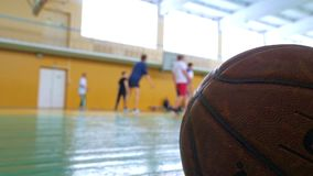 Teens train in the old sports hall. Basketball game. Teens train in the school old sports hall, throw the ball in the basket and run with the ball stock footage