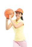 Basketball girl. Vertical shot of an active girl being about to throw the basketball royalty free stock images