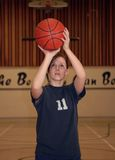 Basketball Girl. A young woman shoots a basketball in a gym Stock Photography