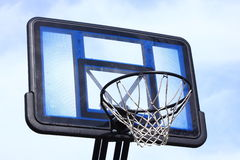 Basketball Goal 1. An outdoor basketball goal photographed against a cloudy blue sky stock photo