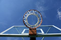 Basketball goal. Looking up at a basketball hoop with blue sky Royalty Free Stock Photo
