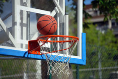 Basketball goal. The ball is almost entering the net royalty free stock image