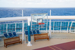 Basketball Goal on Cruise Ship. A basketball goal on the deck of a cruise ship with wood benches and sea in background stock photography