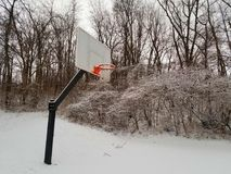 Basketball goal in a snowy Indiana winter. Basketball goal snowy winter royalty free stock photography