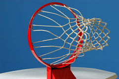 Basketball Goal Viewpoint. An empty basketball goal is seen framed against a blue sky background royalty free stock photography