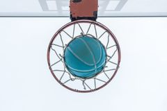 A basketball goes through the net, on a neighborhood playground royalty free stock photo