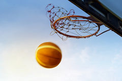 Basketball going through the basket in the blue sky background, soft and blur Stock Photos