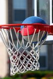 Basketball going through hoop. Striped basketball entering hoop and net Stock Images
