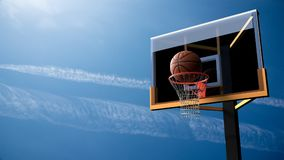 Basketball going into hoop on beautiful blue sky background. Spo Royalty Free Stock Photography