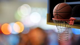 Basketball going into hoop on beautiful bokeh of colorful stadiu Stock Photo