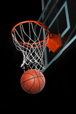 Basketball Going Through Hoop. Isolated over black background Stock Photography