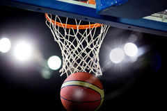 Basketball going through the hoop Stock Photos