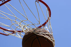 Basketball going through net. Against blue sky stock photography