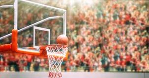 Basketball going through net and scoring during match ,Blurry an. D soft focus Royalty Free Stock Photos