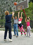 Basketball, grandparents and grandchildren. Basketball between grandmother and grandfather with twins sisters (having fun on holidays). Vertical color photo Royalty Free Stock Photo