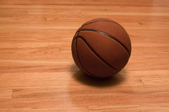 Basketball on the hardwood. Basketball laying on the hardwood floor of the gym Royalty Free Stock Images