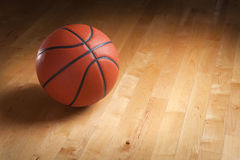 Basketball on hardwood court floor with spot lighting. An orange basketball sits on a hardwood court floor with spot lighting and background that goes from dark Stock Images