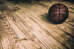 Basketball on Hardwood 2. A basketball laying on the ground of a hardwood court in a gymnasium Royalty Free Stock Photo