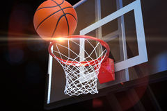 Basketball heading to the net at a sports arena with lens flare . stock images