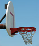 Basketball Hoop. Outdoor basketball hoop and backboard, taken from a side view.  Isolated on blue sky background.Copy space available in upper right of Stock Photography