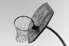 Basketball Hoop. A rusty old basketball hoop against a blue sky in the evening. black and white Stock Photo