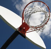 Basketball hoop. Soaring basketball hoop at local playground, outdoors, stands out against mostly sunny skies Royalty Free Stock Photo
