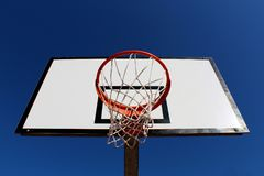 Basketball hoop against blue sky in a playground seen from under the rim Stock Photo