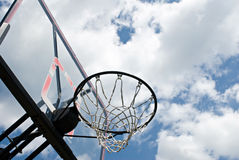 Basketball Hoop Against Clouds. Outdoor basketball hoop and backboard against blue sky with clouds Royalty Free Stock Image
