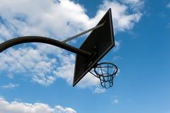 Basketball hoop against a cloudy sky. A basketball hoop against a cloudy sky Royalty Free Stock Images