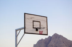 Basketball hoop and backboard. Basketball hoop from below and mountain in background Royalty Free Stock Images