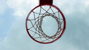 Basketball hoop. The ball is going trough basketball hoop .flying clouds on background.bottom view