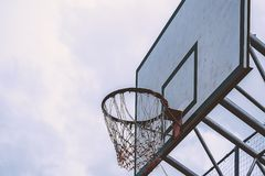 Basketball hoop in a blue day and overcast sky. Added color filter royalty free stock photo