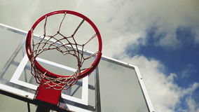 Basketball hoop with cage with clouds in background