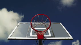Basketball hoop with cage with clouds time lapse footage in background. Royalty Free Stock Images