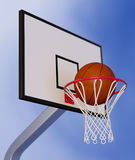 Basketball hoop. Close-up view of a basketball hoop and a ball falling through the hoop, with a blue sky on background (3d render Royalty Free Stock Images