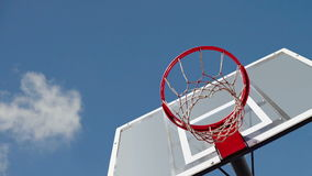Basketball hoop with clouds time lapse footage in background. Royalty Free Stock Photography