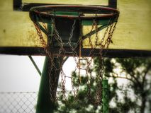 A basketball hoop on a winters day. A basketball hoop on a, cloudy, fence, closeup, basketballcourt, bokeh royalty free stock photo