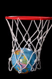 Basketball hoop with earth globe as ball. This stock photo shows a basket being made in a  basketball hoop with the earth / globe as the ball.  Black background Stock Photo