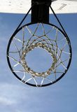 Basketball hoop and net. Low angle underside view of basketball net and hoop with blue sky background Royalty Free Stock Photography