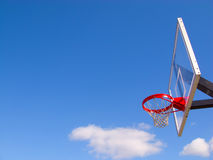 Basketball hoop and net. Basketball hoop and glass backboard with bright red rim and blue Indiana sky Royalty Free Stock Images