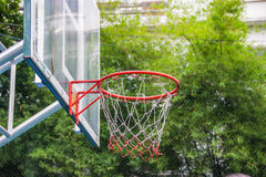 Basketball hoop in the park. With green trees as background Royalty Free Stock Photos