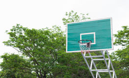 Basketball hoop in the park with green trees as background. Royalty Free Stock Image