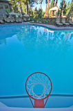 Basketball hoop by pool Royalty Free Stock Photo