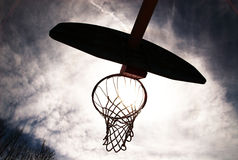 Basketball hoop silhouetted. Basketball hoop shot from underneath. Backlit with sun coming through stock photo