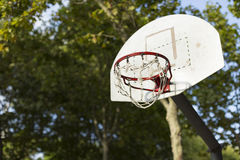 Basketball hoop in sunlight in a park with trees in the background Royalty Free Stock Image