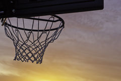 Basketball hoop sunset. Backlit with a glowing sunset Stock Image