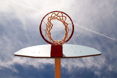 Basketball hoop from underneath. Basketball hoop shot from underneath in a cloudy blue sky royalty free stock image